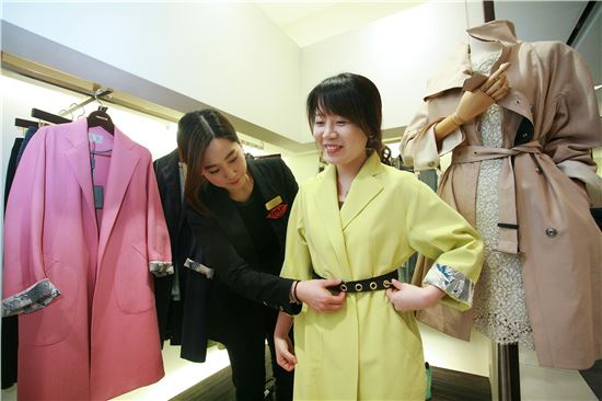 ▲ 한 여성 고객이 의류 브랜드 '타임(TIME)' 매장에서 봄 신상품으로 출시된 트렌치코트를 착용해보고 있다.