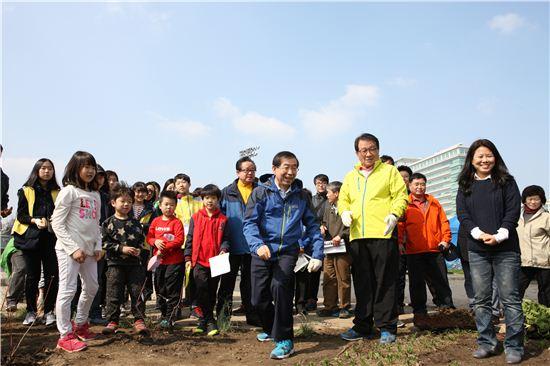 박원순 서울시장과 고재득 성동구청장이 나무심기에 앞서 아이들과 함께 활짝 웃으며 얘기하고 있다.