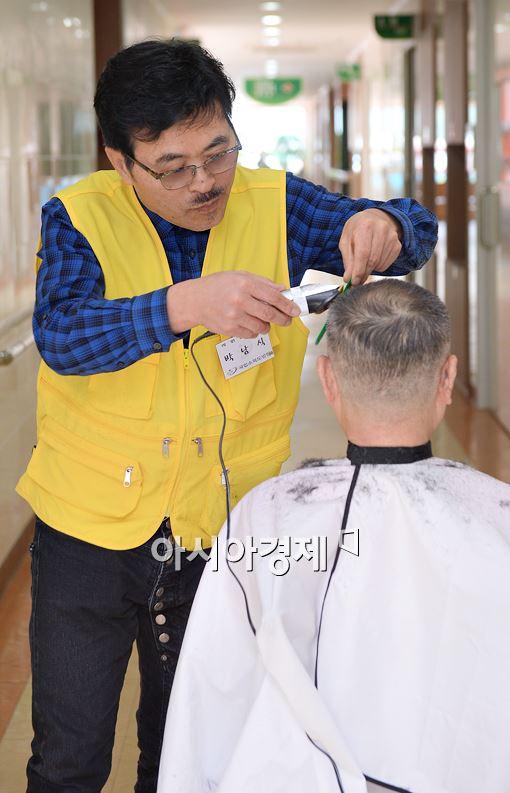 박준 원장이 국립소록도병원에서 한 환우의 머리를 다듬고 있다.