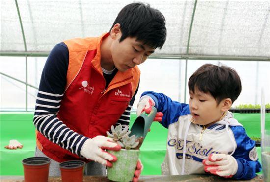 SK케미칼이 식목일을 맞아 경기도 시흥시 소재 행복한 농원에서 지역 아동을 초청해 희망나무심기 행사를 개최했다. 행사에 참가한 아동과 SK케미칼 구성원이 꽃을 심고 있다.