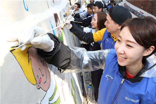 삼성에버랜드 패션부문 2014년 상반기 신입사원 57명이 7일 서울시 서대문구 홍은 1동 호박골을 찾아 마을 벽화를 그리고 있다.