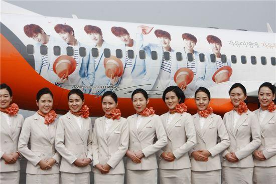 제주항공이 자사 모델인 배우 이민호를 래핑한 항공기를 공개했다. 제주항공 신입 승무원들이 래핑기 앞에서 사진 촬영 중이다.
