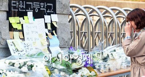 전남 진도 해상에서 여객선 세월호가 침몰한 지 닷새째를 맞고 있는 지난 20일 경기 안산 단원고등학교 정문 앞에서 시민들이 헌화 및 묵념을 하고 있다.