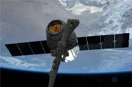 ▲화물 우주선 '드래곤'이 ISS에 정박되고 있다.[사진제공=NASA]