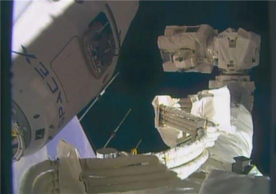 ▲국제우주정거장의 로봇팔이 드래건의 몸체에 거의 다다르고 있다.[사진제공=NASA TV]