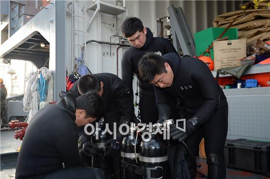 22일 오후 해군 해난구조대(SSU) 대원들이 청해진함 위에서 장비를 손보고 있다. 이들은 직접 바다에 들어가 목숨을 걸고 구조 수색에 들어가는 잠수요원들이다. 사진=공동취재단