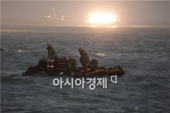 22일 저녁 세월호 침몰 현장에서 해군 구조대원들이 채낚기 어선의 조명 속에 시신을 수색 중이다. 사진=공동취재단