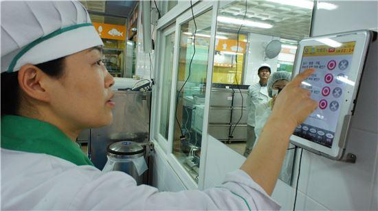▲조리사가 태블릿PC를 이용해 자신의 위생상태를 스스로 점검하고 있는 모습.