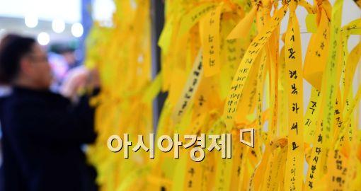 ▲ 시민들이 세월호 사고 실종자들의 귀환을 바라는 염원을 노란 리본에 남겨두고 있다.