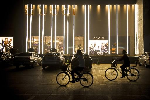 중국 허베이성 스자좡 지역 번화가의 구치 매장 앞을 자전거를 탄 사람들이 지나간다. 사진=블룸버그