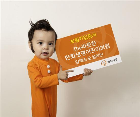 한화생명의 아기 광고모델인 알렉스가 보험가입증서 모형판을 들고 깜찍한 포즈를 취하고 있다.