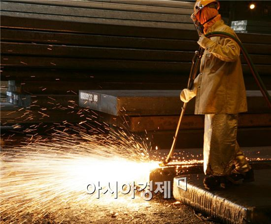 근로자의 날인 1일 광양제철소내에서 조업열기가 뜨겁게 달아오르고 있다.   최상의 완제품을 만들어 내기 위해 직원이 두꺼운 방열복을 입고 두께 23센티미터, 길이 5~10미터의 두꺼운 널빤지 모양의 '슬래브(slab)'를 고르는 작업이 한창이다. 사진제공=포스코 광양제철소