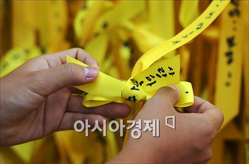 한 시민이 서울광장에 노란리본을 달고 있다.