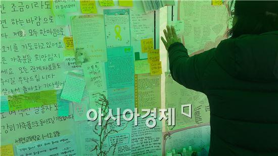 세월호 침몰사고 18일째인 3일 진도 팽목항에서 한 희생학생의 어머니가 딸에게 보내는 쪽지를 붙이고 있다.