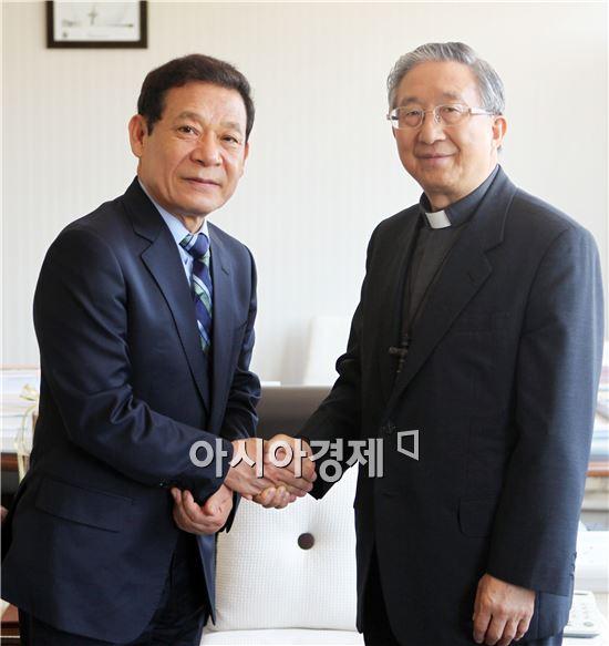 새정치민주연합  공천을 받은 윤장현 광주시장 후보(왼쪽)가 김희중 대주교를 만나 악수를 하고있다.