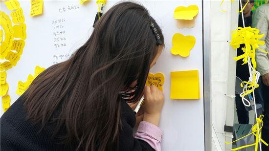 """세월호 침몰사고 19일째인 4일 오전 진도 팽목항을 찾은 한 어린이가 노란색 포스트잇에 고사리같은 손으로 """"언니 오빠 빨리 나아서 얼른 돌아오세요""""라고 쓰고 있다."""
