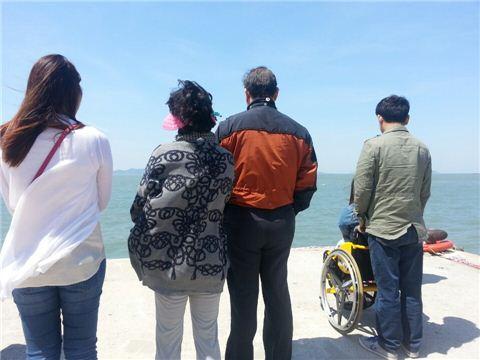팽목항을 찾은 추모객들이 방파제에 서서 바다를 응시하고 있다.