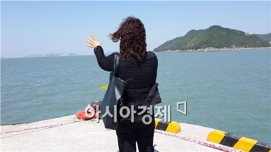 ▲ 5일 오전 전남 진도 팽목항을 찾은 한 어머니가 아이들의 귀환을 염원하며 바다를 향해 손을 내밀고 있다.