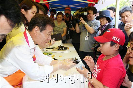 윤장현 광주시장 후보가  안철수 대표와 주먹밥 나누기 행사에 참석해 어린이에게 주먹밥을  나누어주고있다.
