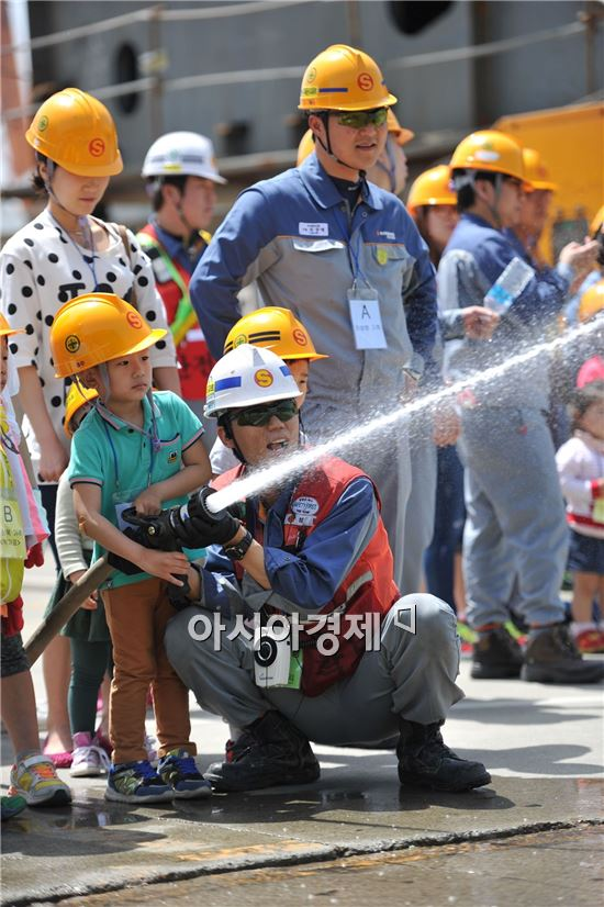 성동조선해양이 지난 16일 임직원 가족을 초청해 '제1회 안전체험의 날' 행사를 개최했다. 임직원 자녀가 회사 직원의 도움으로 소화기로 화재진압 체험을 하고 있다.