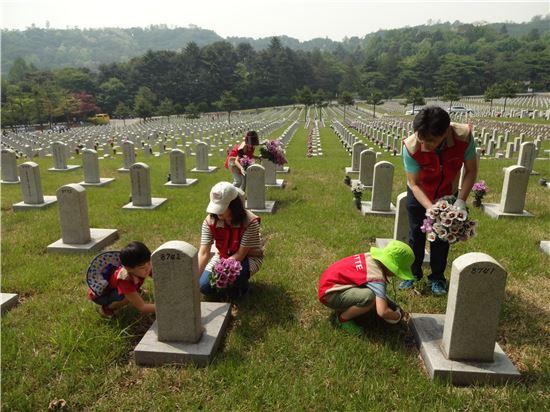 롯데건설 임직원들이 17일 서울 동작구에 위치한 국립 서울 현충원을 방문해 묘비를 닦고 있다.