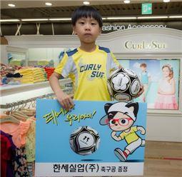 한세실업은 자사의 컬리수 매장에서 당첨된 어린이에게 축구공을 전달하는 행사를 진행했다.