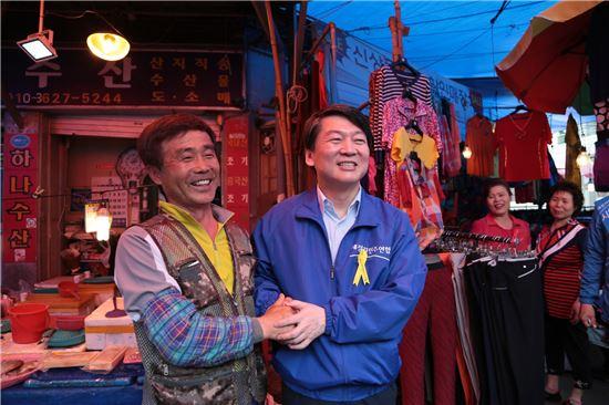 안철수 새정치민주연합 공동대표(오른쪽)가 24일 광주 북구 우산동 말바우시장에서 시장 상인과 악수를 나누고 있다.