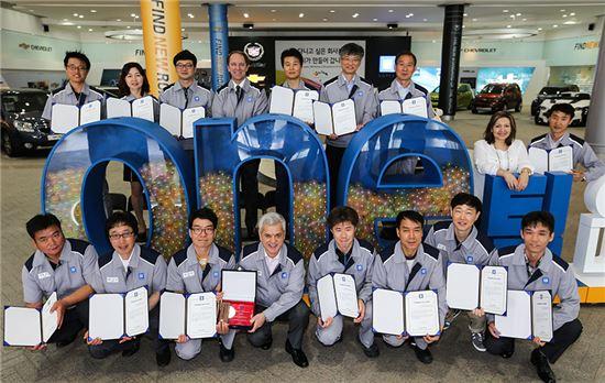 세르지오 호샤 한국GM 사장(사진 맨 앞줄 왼쪽에서 네번째)과 임직원들이 'ONE팀으로 함께 나아갑시다'라는 모형 앞에서 CKD 수출 1000만대 돌파를 기념하고 있는 모습.