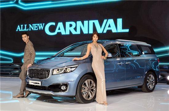 기아차가 '2014 부산모터쇼'에 공개한 올 뉴 카니발(사진 가운데) 옆에서 모델들이 포즈를 취하고 있는 모습.
