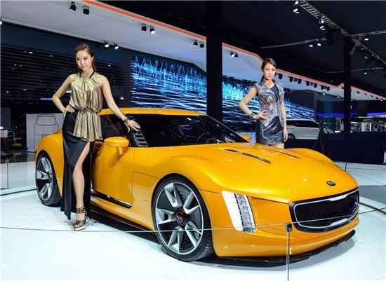기아차가 '2014 부산모터쇼'에서 공개한 GT4 스팅어(사진 가운데) 옆에서 모델들이 포즈를 취하고 있는 모습