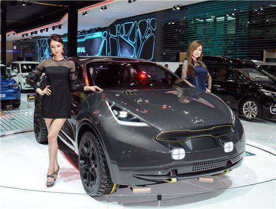 기아차가 '2014 부산모터쇼'에 공개한 콘셉트카 니로(사진 가운데) 옆에서 모델들이 포즈를 취하고 있는 모습