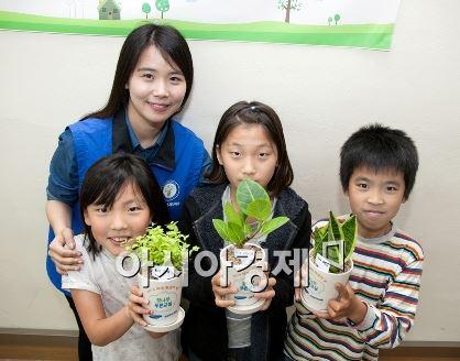 지난 3일 경기도 화성시 청룡초등학교에서 열린 삼성엔지니어링 '찾아가는 환경교실'에서 에코 화분을 받은 학생들과 봉사자가 기념촬영을 하고 있다.