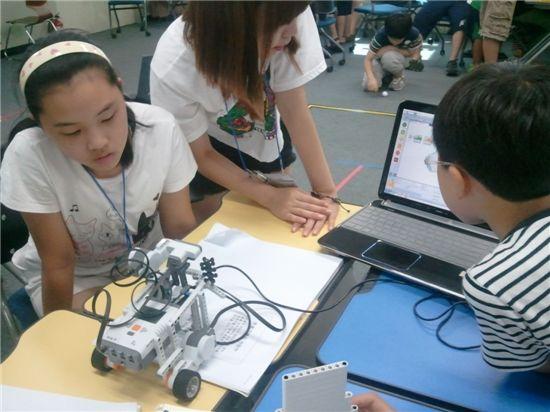 지난해 여름방학 캠프 때 참가학생들이 로봇의 작동원리를 배우고 있다.