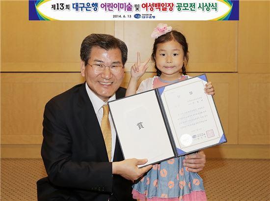 박인규 대구은행장(왼쪽)과 대구은행 2014 어린이미술 공모전 유치원부 금상 박솔비 양.
