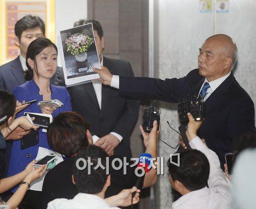 문창극 후보자가 19일 정부서울청사 창성동별관 로비에서 안중근기념관 헌화사진을 들어보이고 있다.