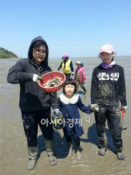 영광 백수해안도로 인근 바닷가에서 가족들이 해산물을 잡고 포즈를 취하고 있다.