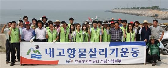 <한국농어촌공사 전남지역본부 직원들이 함평 손불방조제 일대에서 쓰레기를 치운 뒤 수질보전을 위한 캠페인을 벌이고 있다.>