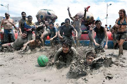 피서객들이 공놀이를 하며 보령머드축제를 즐기고 있다.