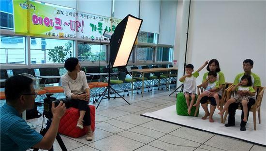 <보성군여성자원봉사협의회가 실시한 '다자녀 가정을 위한 메이크업 및 가족사진 촬영 재능기부' 자원봉사에 참여한 가족이 가족사진을 찍고 있다.>