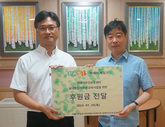 박기택 파티게임즈 이사(오른쪽)가 김범태 북부종합 사회복지관 관장에게 후원금을 전달하고 있다.