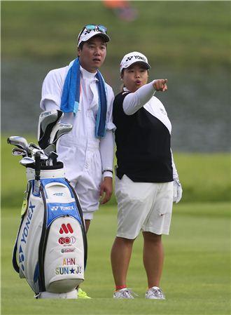 안선주 캐디(왼쪽)가 한화금융클래식 첫날 지정 캐디복의 바지를 걷어올린 채 코스를 살피고 있다. 사진=KLPGA제공
