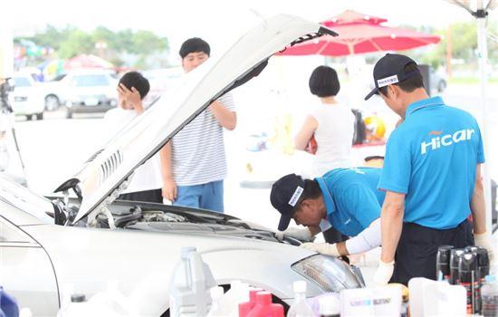 현대해상 서비스 지정점인 하이카프라자의 1급 정비사들이 여름휴가철을 맞아 휴양지에 여행온 고객의 차량을 무상점검하고 있다.