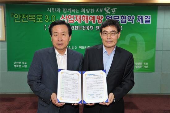 박홍률 목포시장(왼쪽)이 5일 시청 상황실에서 최수봉 안전보건공단 전남서부지사장과 '시민이 행복한 안전도시 목포 만들기'를 위한 협약식을 하고 있다.