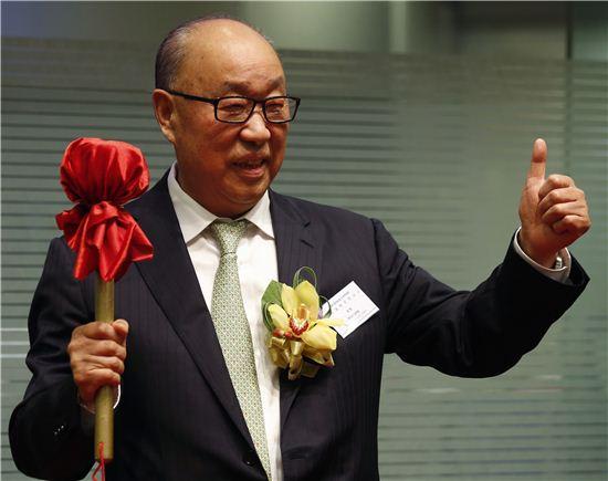 완룽(萬隆) 중국 WH그룹 회장이 5일 홍콩증권거래소에서 상장을 기념해 징을 울린 뒤 엄지손가락을 치켜들어 포즈를 취했다. 사진=블룸버그