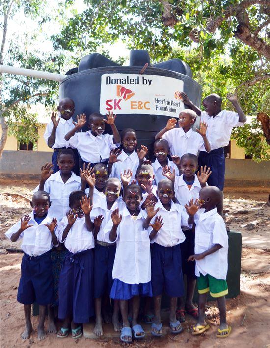 탄자니아 리템베초등학교 학생들이 SK건설이 설치·기부한 물탱크 앞에서 기념촬영을 하고 있다.(출처: SK건설)