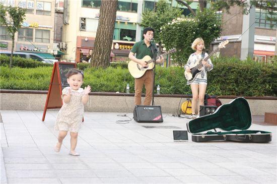 한 어린이가 버스킹 공연이 좋은 듯 박수를 보내고 있다.
