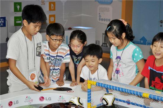 ▲9일 LG디스플레이 '엄마-아빠 회사 탐방' 행사에 참여한 임직원 자녀들이 LG사이언스홀 관람 중 LG로보킹으로 축구경기를 하고 있다.