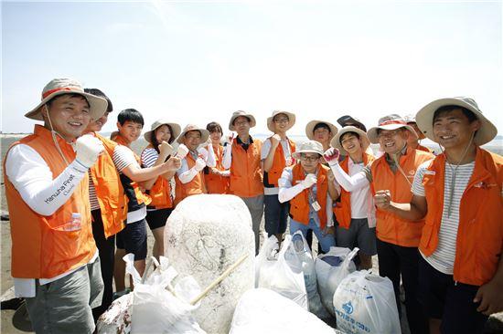 한화생명의 해피프렌즈 청소년봉사단 70여명이 강화도 여차리 갯벌 환경보호를 위해 봉사활동을 하면서 기념촬영을 하고 있다.