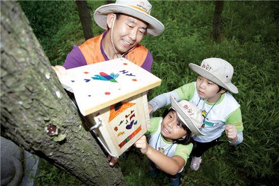 한화생명 임원과 송파 누리미지역아동센터 어린이들이 경기도 성남시 남한산성에서 건강한 숲 생태계 보존을 위해 새집을 직접 만들어 달아주고 있다.