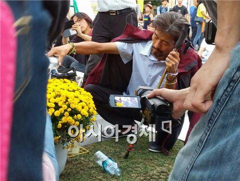 세월호 참사로 희생된 고(故) 김유민 양의 아버지 김영오 씨가 16일 재설치된 천막 농성장으로 돌아와 지팡이를 짚고 화분에 물을 주고 있다. 그는 세월호 참사 진상 규명과 특별법 제정을 촉구하며 34일째 단식을 이어가고 있다.